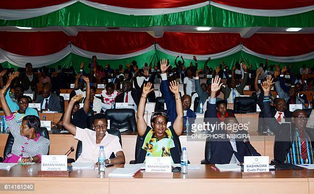 Members of Burundi's National Assembly raise their arm to vote on October 12 2016 in Bujumbura for the withdrawal of the International Criminal Court...