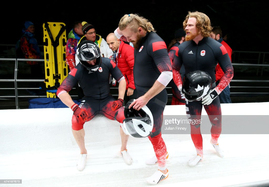 Members of Canada team 3 react after a crash while competing during the Men's Four Man Bobsleigh heats on Day 15 of the Sochi 2014 Winter Olympics at...