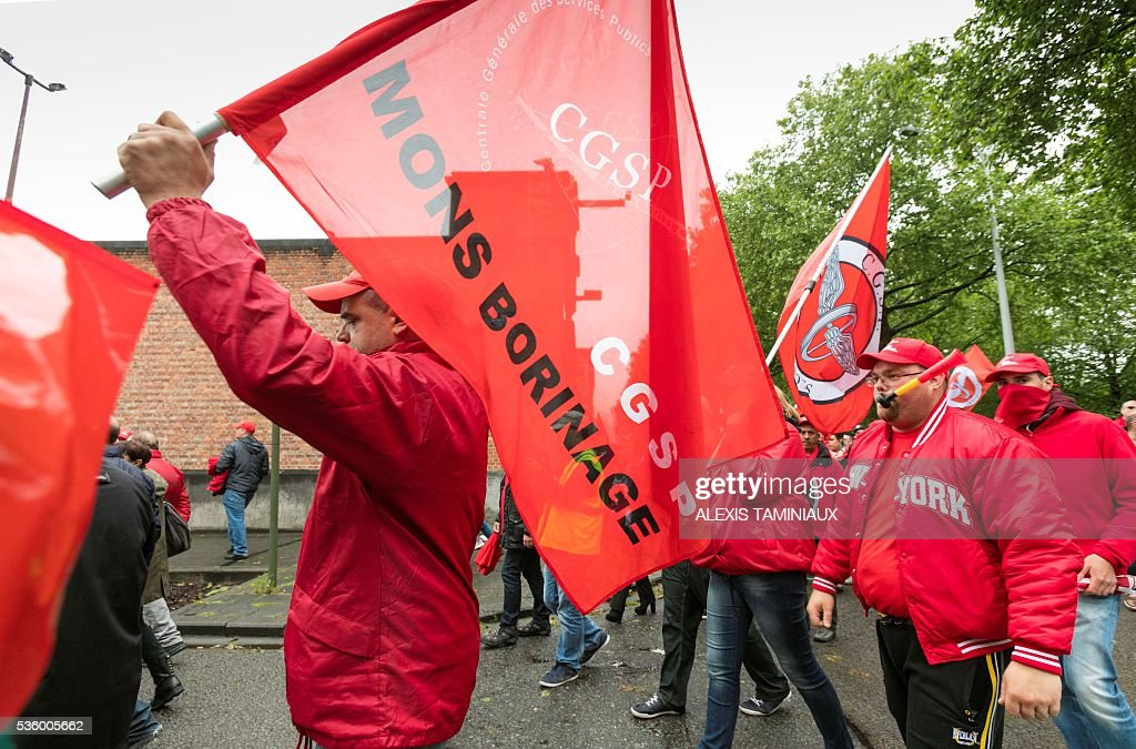 Members of CGSP, Belgian public sector workers's union, hold flags as they march during a protest against the centre-right government's austerity plans on May 31, 2016, in Mons. Belgium faced growing disruption after public sector staff halted work in protest at the government's plans, adding to ongoing strikes on the rail system and in prisons. / AFP / Belga / ALEXIS TAMINIAUX / Belgium OUT