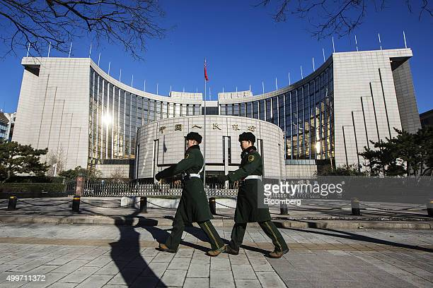 Members of China's People's Liberation Army walk past the People's Bank Of China headquarters in the financial district of Beijing China on Wednesday...