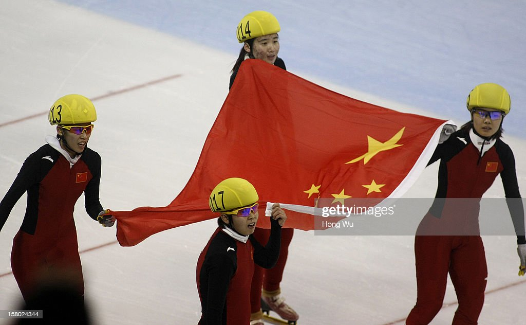 Members of Chinese women's short-track relay team, Kexin Fan, Meng Wang, Xue Kong and Jianrou Li hold their national flag after victory in the Women's 3000m Relay Final, during the day two of the ISU World Cup Short Track at the Oriental Sports Center on December 9, 2012 in Shanghai, China.