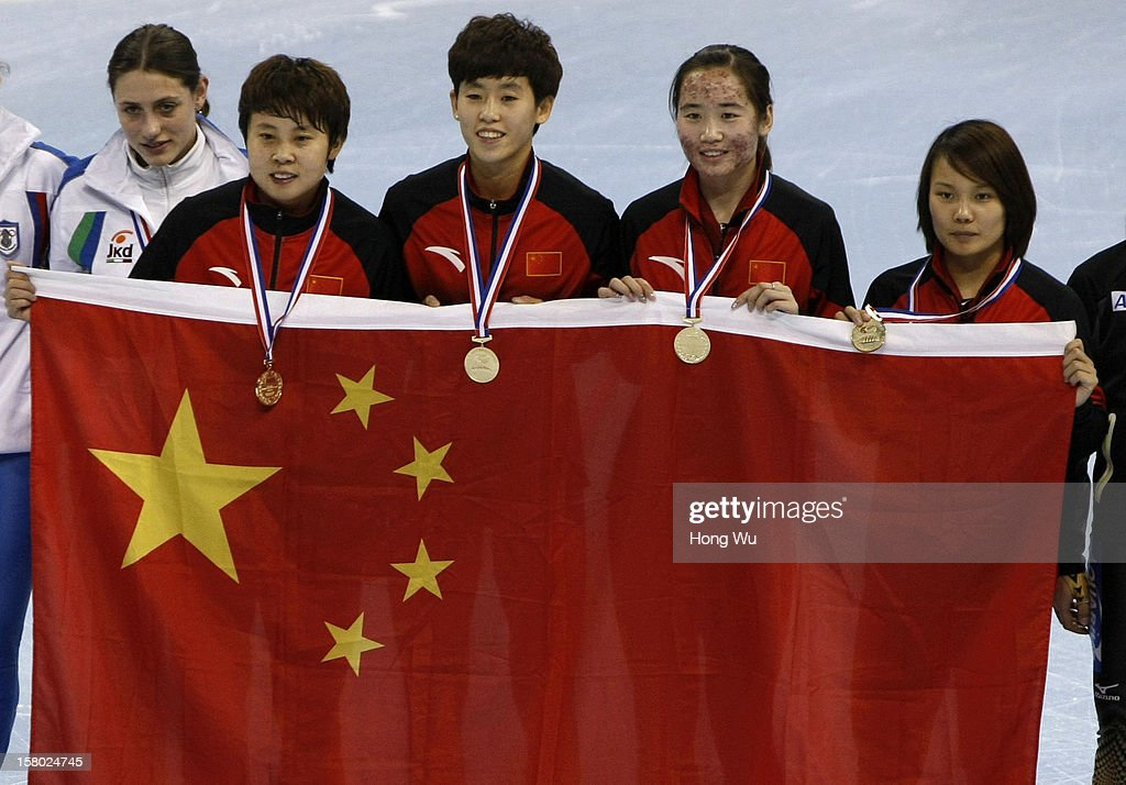 Members of Chinese women's short-track relay team, Meng Wang, Kexin Fan, Xue Kong and Jianrou Li hold national flag to celebrate after won at ceremony of the Women's 3000m Relay Final during the day two of the ISU World Cup Short Track at the Oriental Sports Center on December 9, 2012 in Shanghai, China.