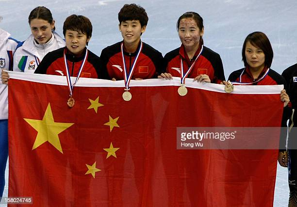Members of Chinese women's shorttrack relay team Meng Wang Kexin Fan Xue Kong and Jianrou Li hold national flag to celebrate after won at ceremony of...