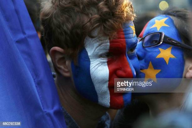Members of civic organization Avaaz with their faces painted in the French and EU flags kiss as they gather with other supporters of French...