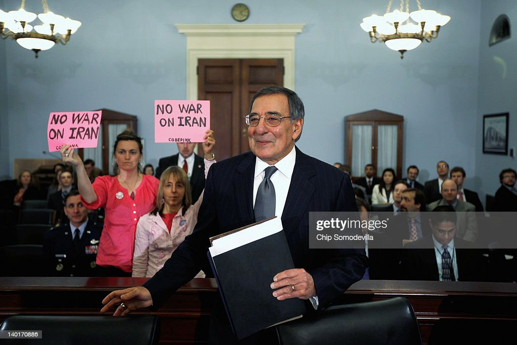 Members of Code Pink for Peace hold up protest signs behind Defense Secretary Leon Panetta as he arrives to testify before the House Budget Committee...