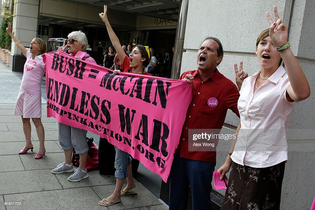 Members of Code Pink including Tighe Barry and Medea Benjamin shout slogans to protest against the war in Iraq as the motorcade of Republican US...