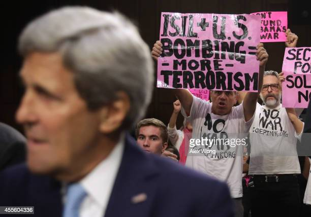 Members of CodePink stage a protest as US Secretary of State John Kerry takes his seat at a hearing before the Senate Foreign Relations Committee...