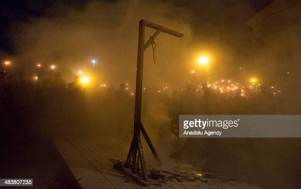 Members of Confederation of Unions of Civil Servants march with torches next to a burned mock gallows during a demonstration to protest the Egyptian...