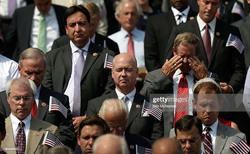 Members of Congress observe a moment of silence during a September 11th remembrance ceremony on the steps of the U.S. Capitol September 11, 2013 in Washington, DC. The nation is commemorating the anniversary of the 2001 attacks which resulted in the deaths of nearly 3,000 people after two hijacked planes crashed into the World Trade Center, one into the Pentagon in Arlington, Virginia and one crash landed in Shanksville, Pennsylvania.