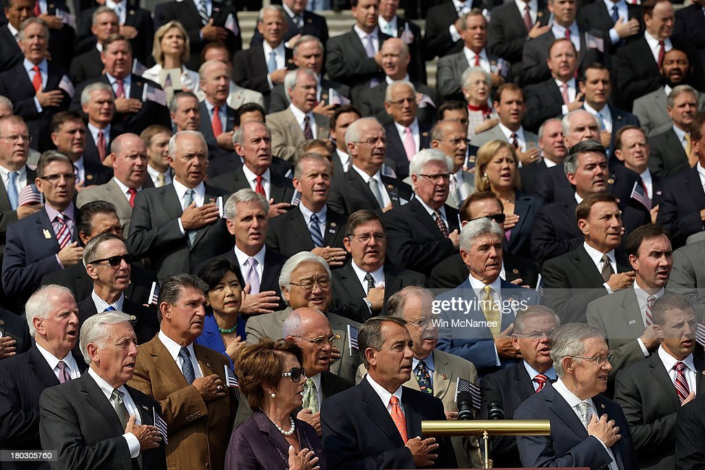 Members of Congress place their hands over their hearts as they sing the national anthem during a September 11th remembrance ceremony on the steps of the U.S. Capitol September 11, 2013 in Washington, DC. The nation is commemorating the anniversary of the 2001 attacks which resulted in the deaths of nearly 3,000 people after two hijacked planes crashed into the World Trade Center, one into the Pentagon in Arlington, Virginia and one crash landed in Shanksville, Pennsylvania.