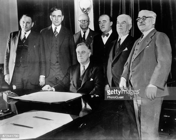 Members of Congress pose with American politician US President Franklin D Roosevelt at the signing of the CullenHarrison Act which once again...