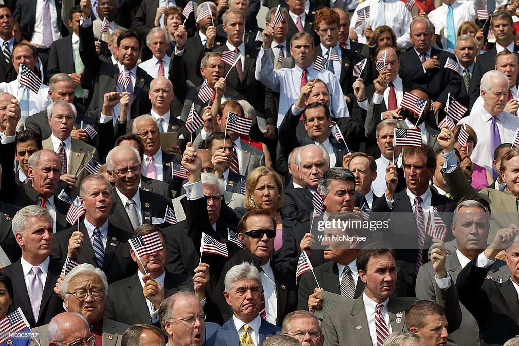 Members of Congress wave American flags as they sing 'God Bless America' during a September 11th remembrance ceremony on the steps of the U.S. Capitol September 11, 2013 in Washington, DC. The nation is commemorating the anniversary of the 2001 attacks which resulted in the deaths of nearly 3,000 people after two hijacked planes crashed into the World Trade Center, one into the Pentagon in Arlington, Virginia and one crash landed in Shanksville, Pennsylvania.