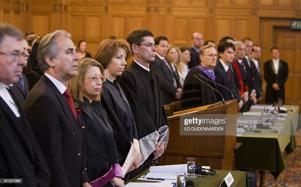 Members of Croatia's legal team (L) and of Serbia's (R) stand on May 26, 2008 in The Hague before the International Court of Justice hearing of a complaint filed in 1999 by Croatia against Serbia, alleging a program of 'ethnic cleansing' during the 1991-1995 war in Croatia was directly controlled from Belgrade. Serbia argued before the UN's highest court on May 26, 2008 that crimes committed in the early 1990s war in Croatia did not amount to an act of genocide as alleged a complaint filed by Zagreb. AFP PHOTO / ED OUDENAARDEN -Netherlands out - Belgium out-