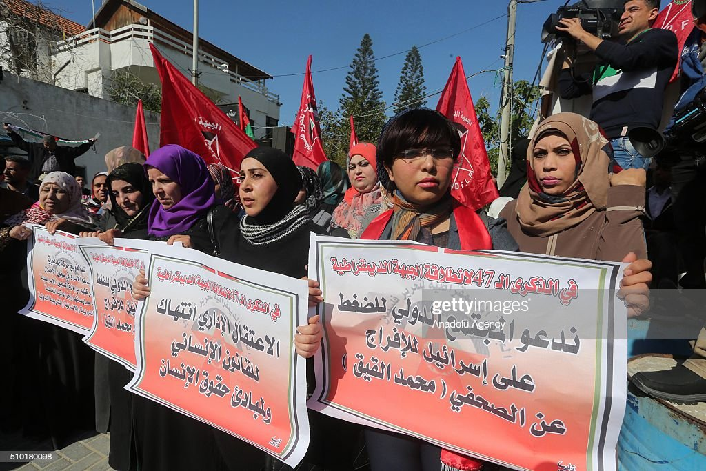 Members of 'Democratic Front for the Liberation of Palestine' hold banners during a protest for release of journalist Muhammed el-Kayk, who stages a hunger strike in an Israeli prison, in front of UNSCO building in Gaza City, Gaza on February 14, 2016.