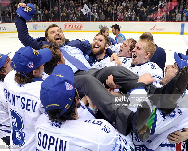 Members of Dinamo celebrate with coach Oleg Znarok after Dinamo Moscow defeats Traktor Chelyabinsk at the final playoff game during the KHL...