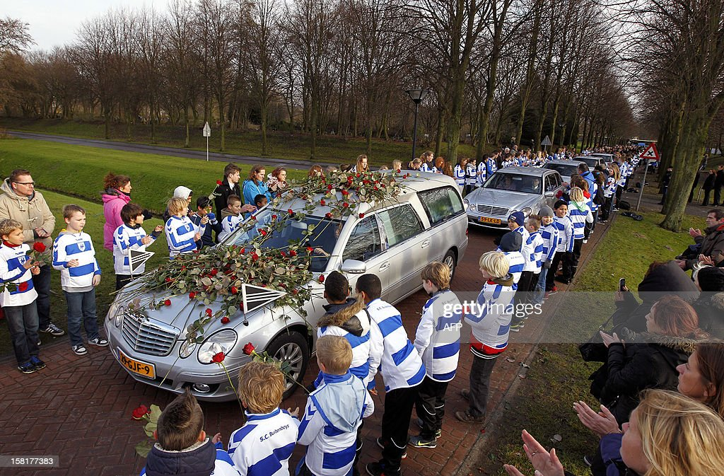 Members of Dutch football club SC Buitenboys wearing the colors of the club stand to they pay respect to Dutch linesman Richard Nieuwenhuizen as the hearse carrying the body of Nieuwenhuizen arrives at the crematory in Almere, on December 10, 2012. Nieuwenhuizen collapsed and fell into a coma after he was attacked by three teenagers at the end of a junior club football match on December 2, 2012. AFP PHOTO / ANP / BAS CZERWINSKI -netherlands out -