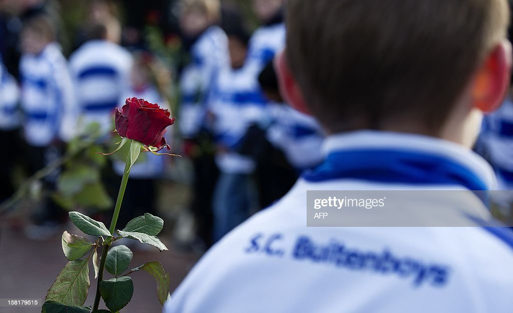 Members of Dutch soccer club SC Buitenboys hold roses as they wait for the arrival of the hearse carrying to the crematory the body of Richard Nieuwenhuizen, a soccer linesman who died after he was assaulted at the end of a youth game a week ago, on December 10, 2012 in Almere. AFP PHOTO/ANP BAS CZERWINSKI