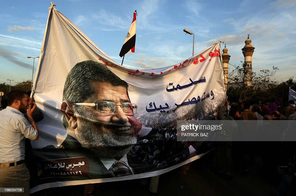 Members of Egypt's Muslim Brotherhood carry a banner with a picture of Egyptian President Mohamed Morsi during a rally in Cairo on December 11, 2012. Protesters gathered in Cairo for rival rallies over a deeply disputed constitutional referendum proposed by Egypt's Islamist president, Mohamed Morsi, raising fears of street clashes. AFP PHOTO/PATRICK BAZ