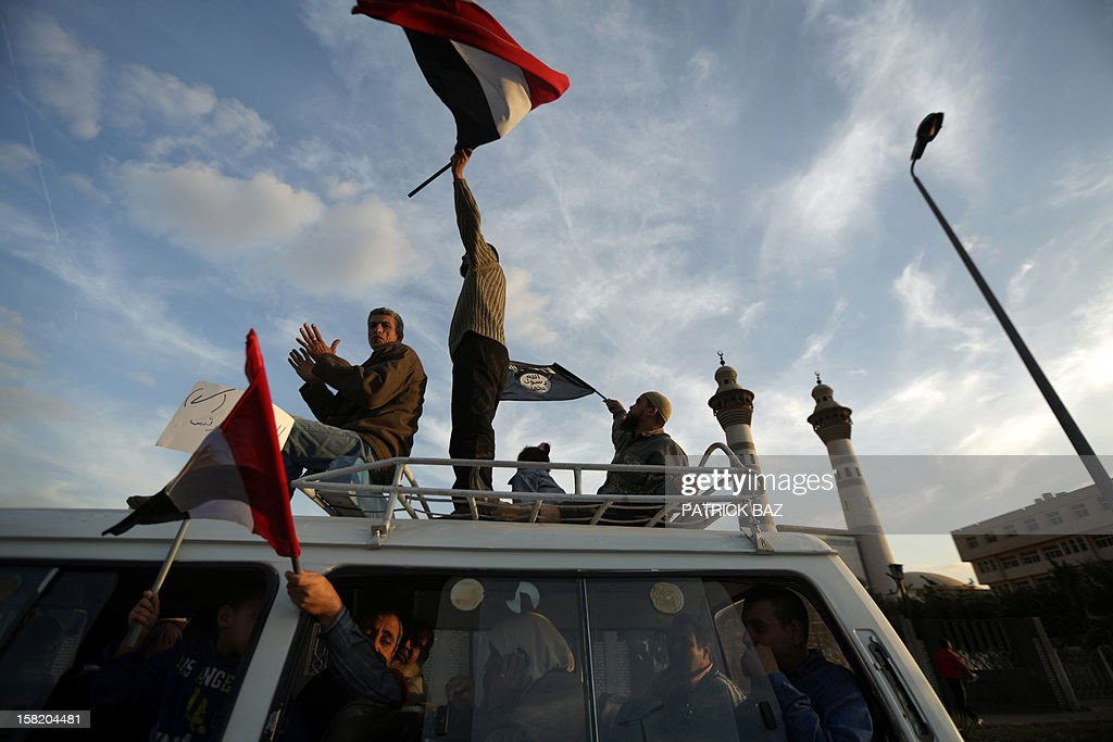 Members of Egypt's Muslim Brotherhood wave their national flag and an al-Qaeda affiliated banner (R) as they parade in Cairo on December 11, 2012. Protesters gathered in Cairo for rival rallies over a deeply disputed constitutional referendum proposed by Egypt's Islamist president, Mohamed Morsi, raising fears of street clashes. AFP PHOTO/PATRICK BAZ