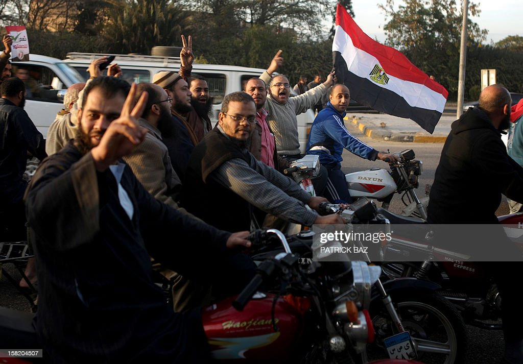Members of Egypt's Muslim Brotherhood wave their national flag as they parade in Cairo on December 11, 2012. Protesters gathered in Cairo for rival rallies over a deeply disputed constitutional referendum proposed by Egypt's Islamist president, Mohamed Morsi, raising fears of street clashes. AFP PHOTO/PATRICK BAZ