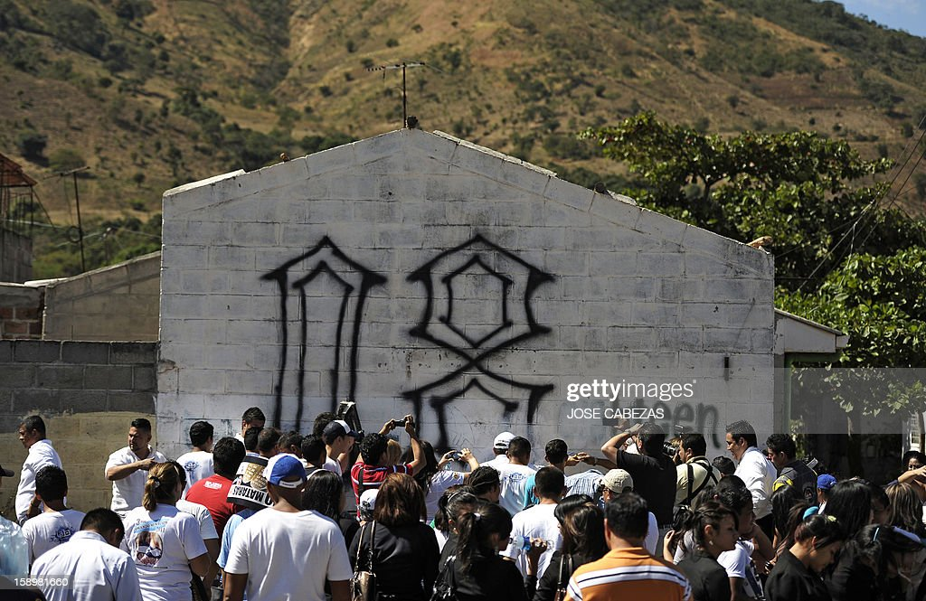 Members of El Camino Christian Church and journalists gather by a graffiti of the 'Mara 18' gang before it is erased at Valle del Sol neighborhood in Apopa, 14 km north of San Salvador, El Salvador on January 4, 2013. Raul Mijango, Gang truce mediator, announced that 18 districs in El Salvador will be considered 'Sanctuary Territories' for gangs as a second stage of the gang truce. AFP PHOTO/ Jose CABEZAS