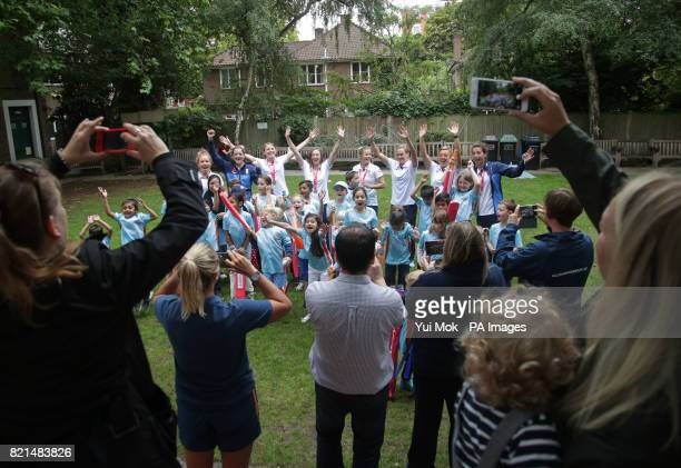 Members of England women's cricket team pose for a photograph with children from the All Stars Cricket programme during a media call at Lord's London