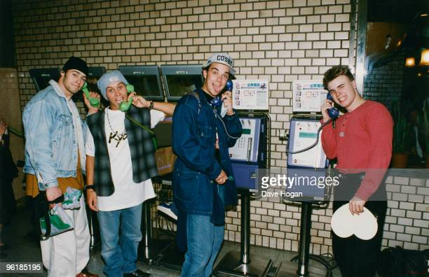 Members of English boy band Take That make phone calls during a visit to Japan circa 1995 From left to right Howard Donald Mark Owen Robbie Williams...