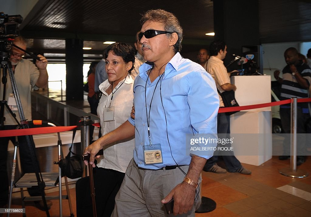Members of FARC-EP leftist guerrillas delegation commander Jesus Santrich (R) and guerrilla fighter Maritza Garcia (L) arrive at the Convention Palace in Havana for the peace talks with the Colombian government, on December 6, 2012.