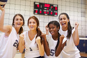 Members Of Female High School Volleyball Team Smiling To Camera