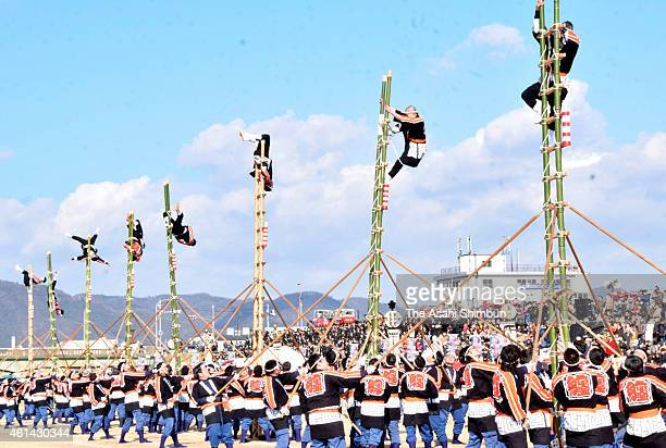 Members of fire companies balance on top of bamboo ladders as they perform ladder stunts during the New Year's fire review on January 11 2014 in...