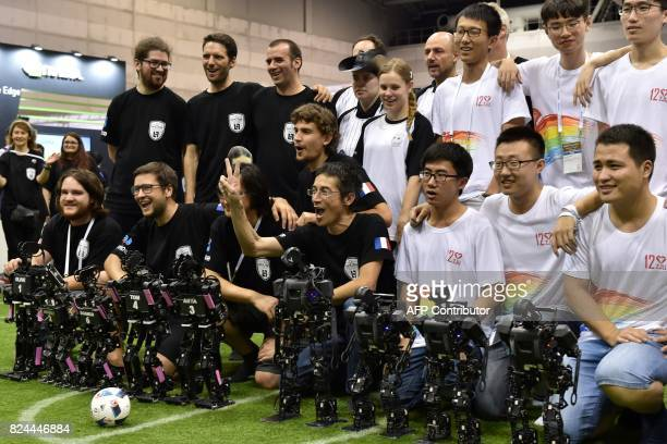 Members of France's Bordeaux University celebrate their victory in the kidsize android football tournament final against China at the RoboCup 2017 in...