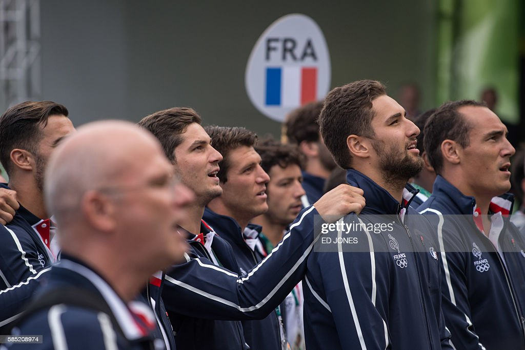Members of France's Olympic team sing the national anthem as they attend a welcoming ceremony at the athletes village of the Rio 2016 Olympic Games...