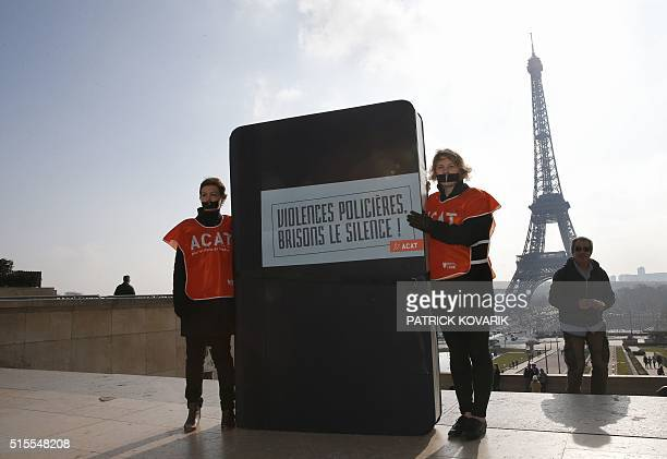 Members of French NGO Action of Christians for the Abolition of Torture stand next to a giant book with scotch tape on the mouth on March 14 2016 in...