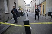 Members of French riot police stand guard at the entrance of a cordened off area outside a building in the northern Paris suburb of SaintDenis on...