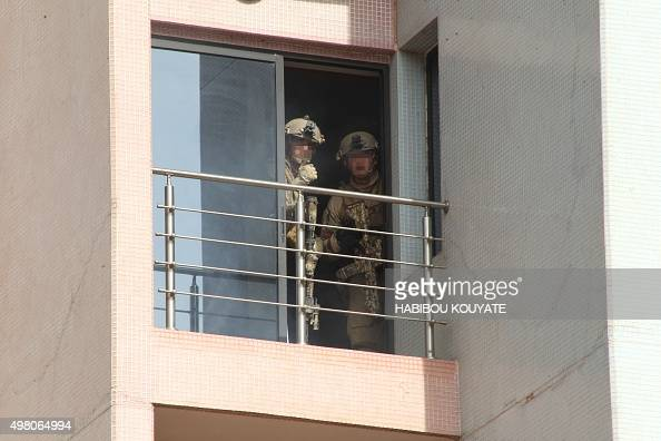 Members of French special forces look out from a window of the Radisson Blu hotel in Bamako on November 20 after the assault of security forces...
