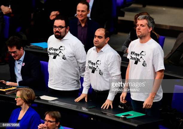 Members of German environmental Greens party 'Die Gruenen' Chris Kuehn Ozcan Mutlu and Dieter Janecek stand up wearing a Shirt reading 'Free Deniz'...