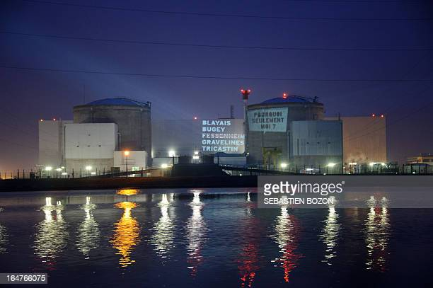 Members of Greenpeace projects texts reading Blayay Bugey Fessenheim Gravelines Tricastin why me only on the nuclear powerplant of Fessenheim in...