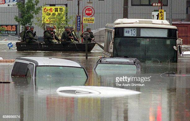Members of Ground SelfDefense Force row a boat among submerged cars and buses to continue rescue operation after torrential rainfall on September 12...