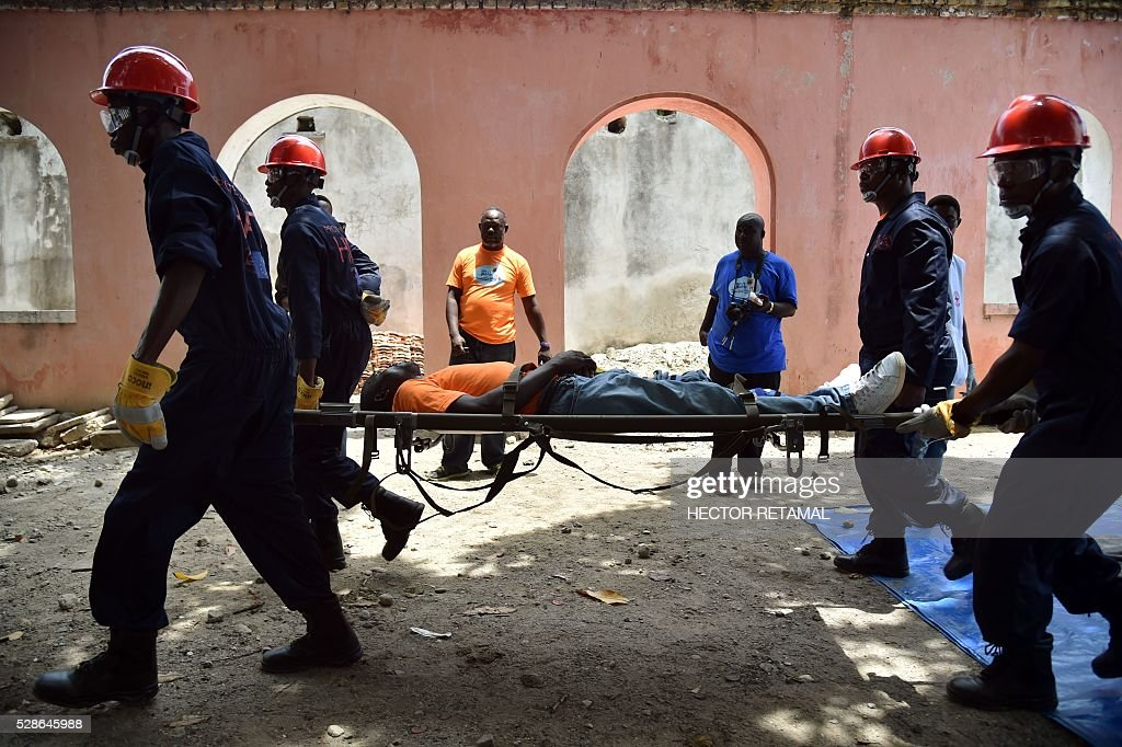 Members of Haitian Civil Protection rescue victims during the Eartquake and Tsunami Emergency drill in Cap-Haitien, Haiti, on May 6, 2016. The simulation exercise was organised by the Civil Protection Directorate, with the support of the UN Development Programme (UNDP). An estimated 4,500 people participated in the activities during the simulacre. / AFP / HECTOR
