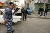 Members of Hamas' security forces inspect cars in the Gaza border town of Rafah on April 16 after a radical Islamist group killed an Italian activist...