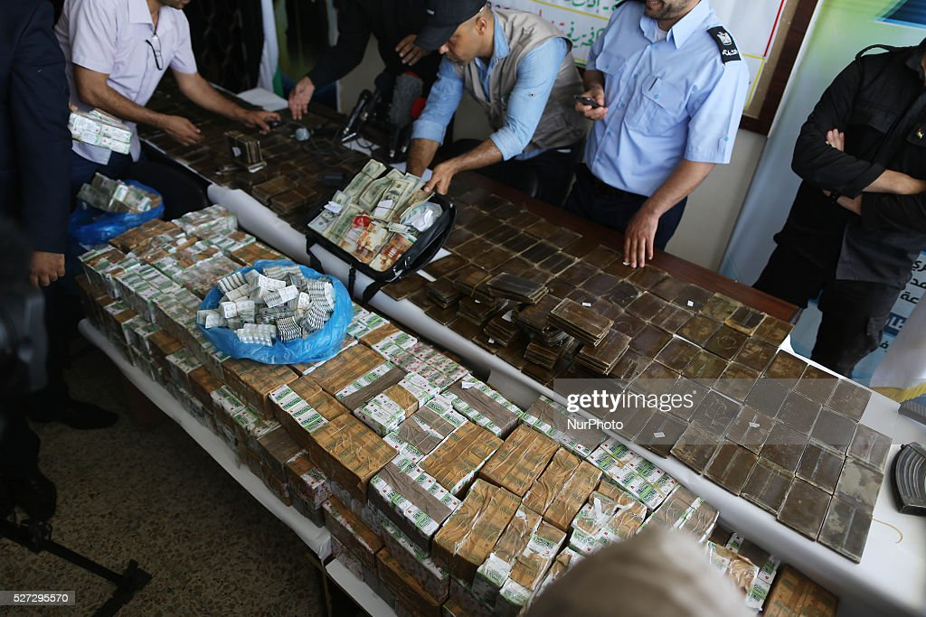 Members of Hamas' security forces stand near drugs that were seized by forces in front of the media in Gaza City on May 2, 2016.
