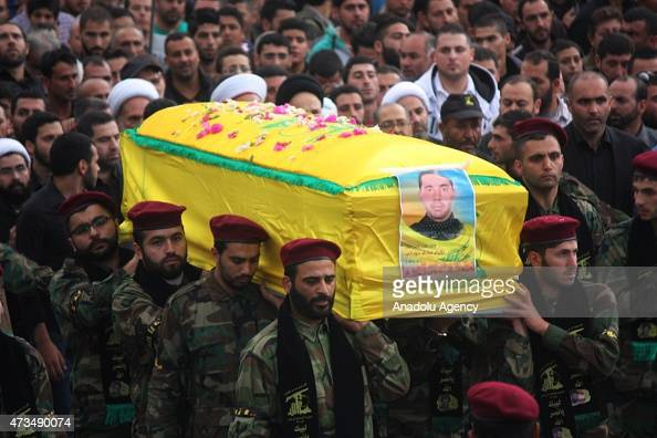Members of Hezbollah carry the coffin of Ali Mohamed Hamada killed fighting alongside Syrian Government forces in Qalamun during his funeral in Srifa...