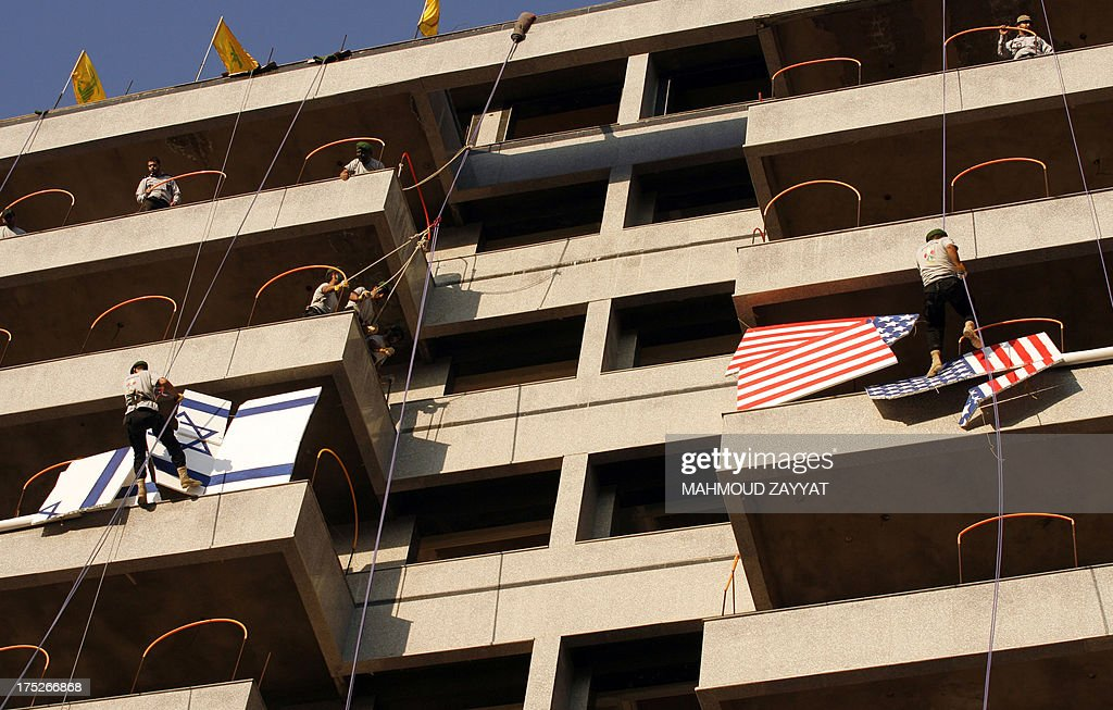 Members of Hezbollah's al-Mehdi scouts abseils down a building and break polystyrene sheets bearing the American and Israeli flags, during a parade in the Lebanese southern suburb of Nabatiyeh, on August 1, 2013, to mark the 'Al-Quds (Jerusalem) International Day'. An initiative started by Iranian revolutionary leader Ayatollah Ruhollah Khomeini, Quds Day is held annually on the last Friday of the Muslim fasting month of Ramadan and calls for Jerusalem to be returned to the Palestinians.