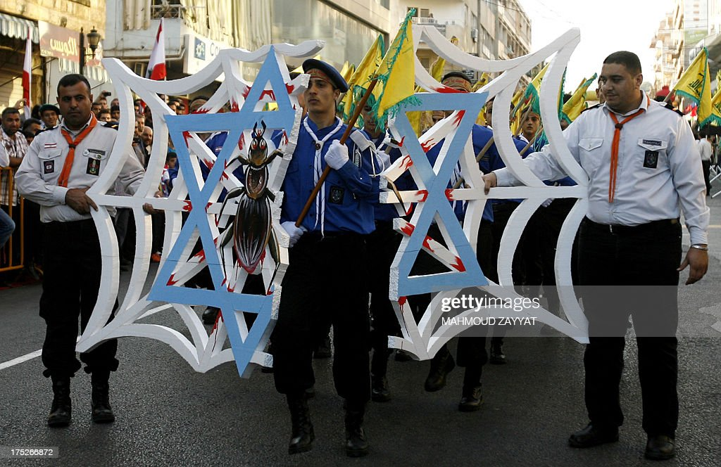 Members of Hezbollah's al-Mehdi scouts march through a Spider web made from polystyrene, during a parade in the Lebanese southern suburb of Nabatiyeh, on August 1, 2013, to mark the 'Al-Quds (Jerusalem) International Day'. An initiative started by Iranian revolutionary leader Ayatollah Ruhollah Khomeini, Quds Day is held annually on the last Friday of the Muslim fasting month of Ramadan and calls for Jerusalem to be returned to the Palestinians. The spider web is a reference to a comment made years ago by Hezbollah leader Hassan Nasrallah claiming that Israel is weaker than a cobweb.