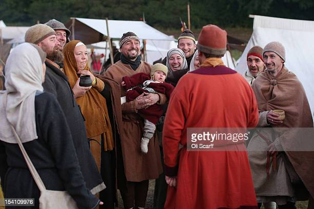 Members of historical reenactment groups assuming the role of Norman soldiers share a joke in their encampment after the annual reenactment of the...