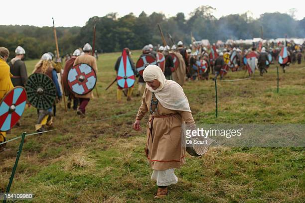 Members of historical reenactment groups assuming the role of Saxon and Norman soldiers leave the battlefield after the annual reenactment of the...