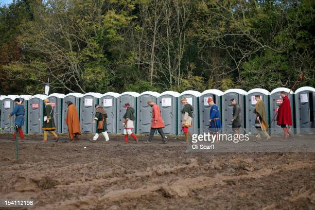 Members of historical reenactment groups walk past a row of portable toilets prior to the annual reenactment of the Battle of Hastings at Battle...