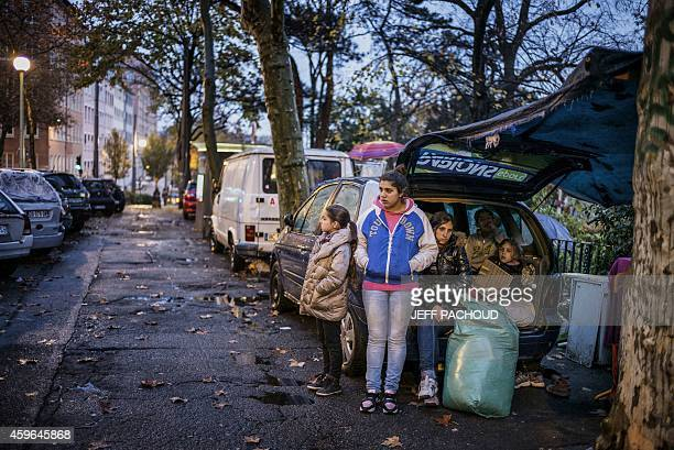 Members of homeless families whose children attend school stand next to their cars after spending the night in a shelter with the help of the 'Jamais...