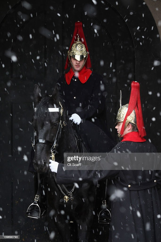 Members of Household Cavalry guard the entrance to Horse Guards Arch as snow falls on January 18, 2013 in London, England. Widespread snowfall is affecting most of the UK with school closures and transport disruption. The Met Office has issued a red weather warning for parts of Wales, advising against all non-essential travel as up to 30cm of snow is expected to fall in some areas today..