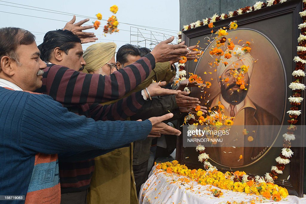 Members of Human Rights Protection Council pose as they shower flower petals on a portrait of Indian Sikh independence activist Shaheed Udam Singh, on his 113th birth anniversary, in Amritsar on December 26, 2012. Singh assassinated Michael O'Dwyer in 1940, the colonial Lieutenant Governor of Punjab who supported the British Army's involvement in the Jallianwala Bagh massacre, also known as the Amritsar massacre. AFP PHOTO/NARINDER NANU
